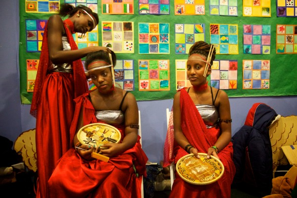 Dancers Saluwa Umuhoza (left), Aline Cyuzuzo (center)and Nadia Umwali of the Abeza B'Inganzo Troop prepare in the dressing room before performing at the fourth annual International Women's Day Fashion Show in Portland on Friday night.