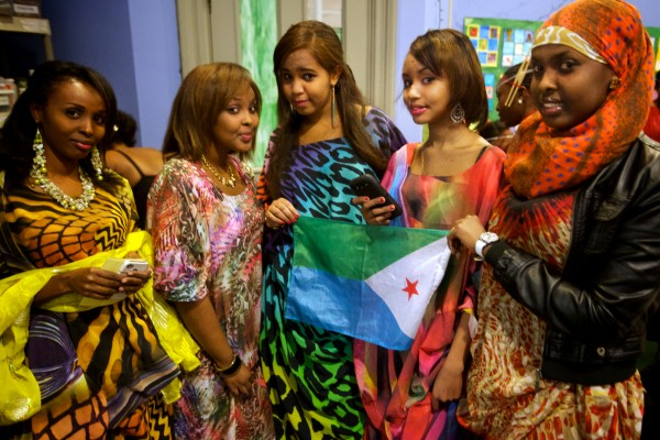 A group of friends Rabia Ismail (left), Asthma Ahmed, Asthma Ahmed (same name) Soumeya Abdillani and Awo Ahmed hold the flag of their native Djibouti backstage before walking the runway at the fourth annual International Women's Day Fashion Show in Portland on Friday night.