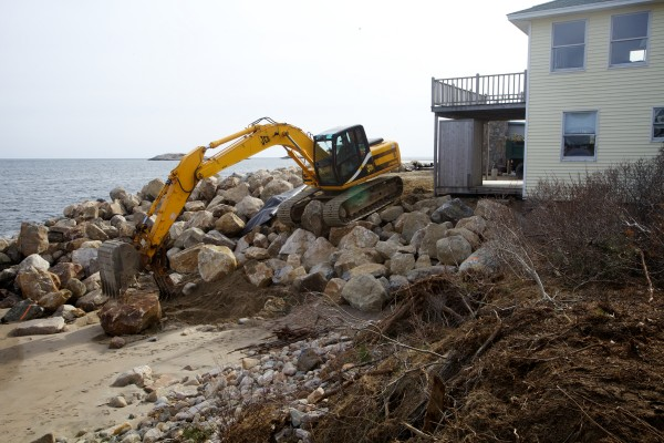 Dan Delano of D&S Excavators works to place tons of rock in front of a string of buildings at Popham Beach in Phippsburg Monday. Delano has been working since January to protect the structures after nearly a decade of erosion washed away beach and 40 feet of lawns.