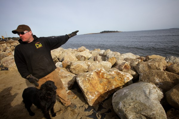 Dan Delano of D&S Excavators points to where nearly a decade of erosion washed away beach and lawns in front of several buildings at Popham Baech in Phippsburg. Delano has been working since January, placing tons of rock in front of the buildings to try and protect them from ocean waves.