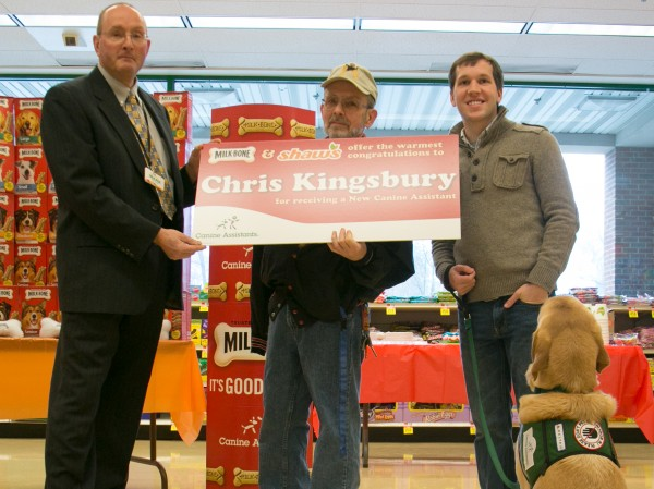 Shaw's store director Mark Robson (left) presents a large check to Chris Kingsbury (center) along with Canine Assistance trainer Kevin Balance (right) and his service dog representative, Henry, at the Shaw's supermarket on Main Street on Wednesday, March 13, 2013. Kingsburg will receive a donated assistance dog from Shaw's and Milk-bone sponsorship program.