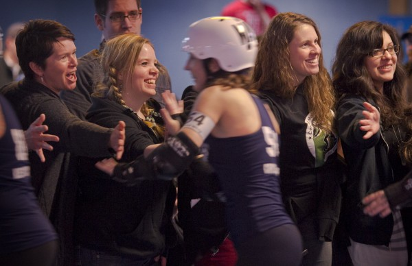 Fans line the rink to slap high-fives with the players after the bout, Saturday, March, 9, 2013, in Portland.