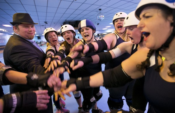 The Port Authorities and their coach, &quotCaesar Foulin',&quot let out a cheer before the start of the second half of a bout against the Rock Coast Rollers, Saturday, March, 9, 2013, in Portland.