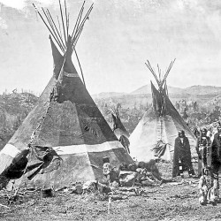 "Shoshone Indians stand amidst the skin teepees (or ""lodges"") they have erected at a camp somewhere in the Rockie Mountains circa 1860-1870. William Farnham of Bangor marched with California infantrymen in late January 1863 to attack a similar Shoshone camp along the Bear River in Washington Territory. In a letter to his parents, Farnham compared the battle to fighting Confederate troops back east."