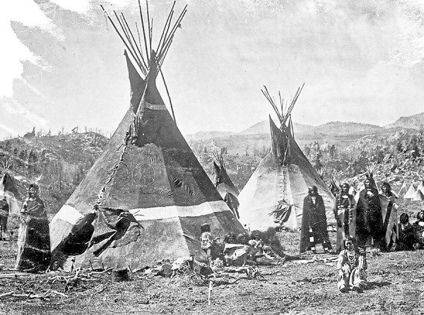 Shoshone Indians stand amidst the skin teepees (or &quotlodges&quot) they have erected at a camp somewhere in the Rockie Mountains circa 1860-1870. William Farnham of Bangor marched with California infantrymen in late January 1863 to attack a similar Shoshone camp along the Bear River in Washington Territory. In a letter to his parents, Farnham compared the battle to fighting Confederate troops back east.