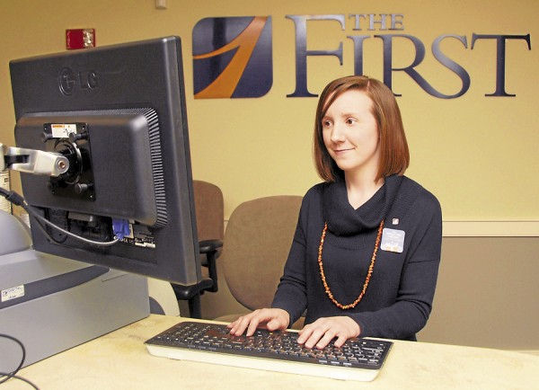 Torie LeBreton, a retail banking associate at The First's new branch at 145 Exchange St., Bangor, stands at her assigned pod inside the bank. Photo taken on Monday, Feb. 25, 2013.
