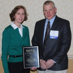 Judy Wallingford, president of Maine Water Company, receives the prestigious Jeff Nixon Award from Jon Ziegra, president of the Maine Water Utilities Association.