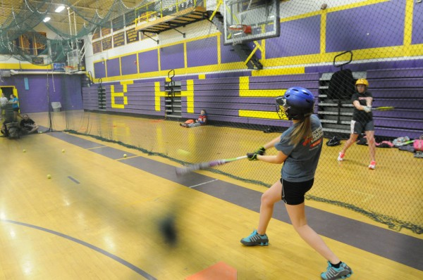 Bucksport High School student Tyler DuPont swings on tennis balls during the first softball try out of the season at Bucksport High School on Monday.
