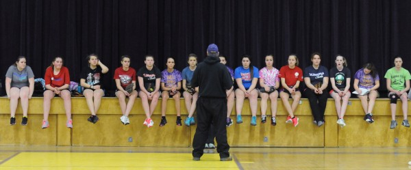 Bucksport High School students sit on the gym stage as they are instructed by softball coach Mike Carrier during the first softball try out of the season at Bucksport High School on Monday.