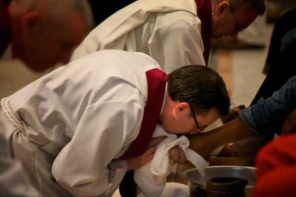 Rev. Frank Murray kisses a community member's foot after washing it at the Cathedral of the Immaculate Conception in Portland Thursday. The ceremony mimics how Jesus humbly washed his disciples' feet before the Last Supper. The service aimed to raise awareness of suffering in the community.