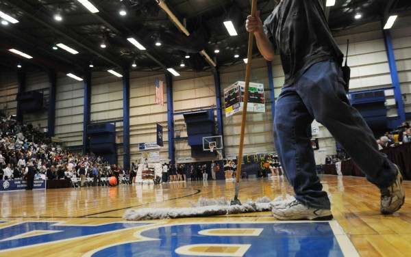 A final sweep of the floor by a maintenance technician readies the playing surface for the final game of high school tournament action at the Bangor Auditorium on Saturday. The aging facility is to be torn down later this year.