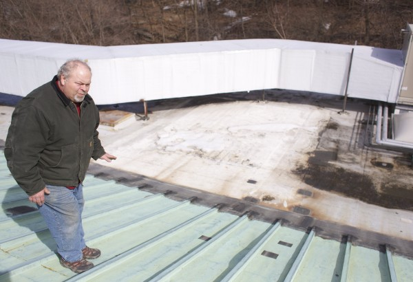 Terry Bladen, the Bangor Public Library's head of maintenance, looks over the copper roof of the library that is in disrepair. The library needs $3 million to replace the roof, which has outlived its use and is causing water damage in parts of the building.