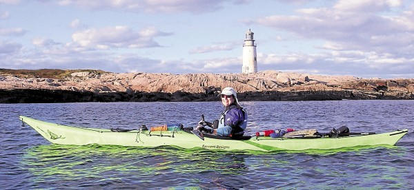 Master Maine Guide Karen Francoeur paddles past Mistake Island's Moose Peak Lighthouse on a tour of the islands near Great Wass Island off Jonesport-Beals. The 72-foot tower marks the entrance to Main Channel Way and Eastern Bay.