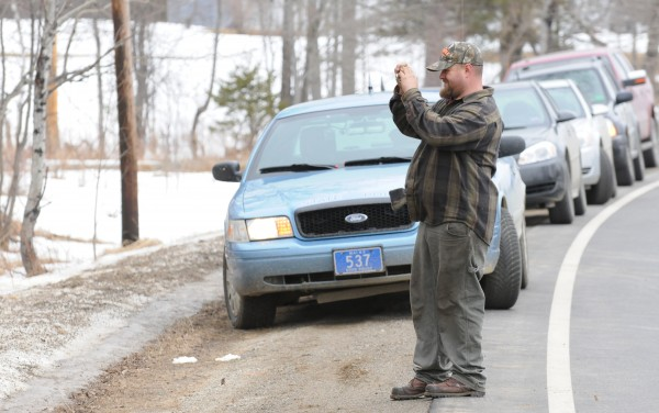 A neighbor takes a picture of police on the property of Lawrence Lewis at 450 Macwahoc Road in Molunkus on Tuesday.