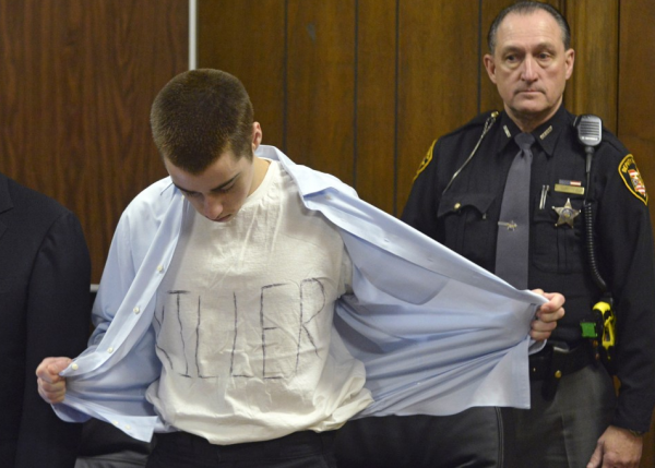 T.J. Lane unbuttons his shirt to reveal &quotkiller&quot written on his t-shirt during sentencing Tuesday, March 19, in Chardon, Ohio.