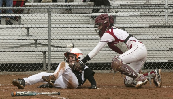 Brewer's Delaney Davis, left, slides into home plate against Bangor's Kylie Cunningham on Wednesday, April 24, 2013.