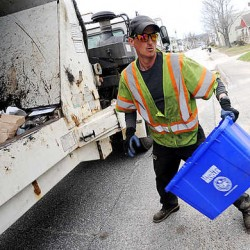 Matt Greenwood from Almighty Waste empties recycling bins along Acadia Avenue in Lewiston on Thursday morning.