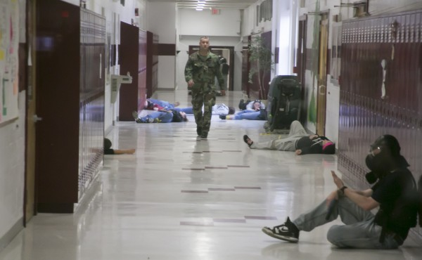 Sgt. Scott Wilcox of the Orono Police Department walks the halls at Orono High School after a live shooter drill with Husson University criminal justice students on Saturday.