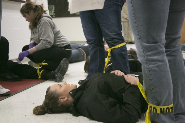 Husson University junior Ariel Vanadestine pretends to have an abdominal wound during a live shooter drill with Husson criminal justice students at Orono High School on Saturday.