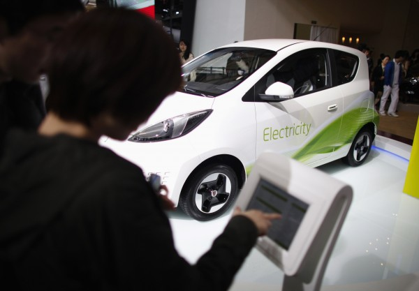 A couple looks at a Morris Garage electric car during the 15th Shanghai International Automobile Industry Exhibition in Shanghai April 21, 2013.
