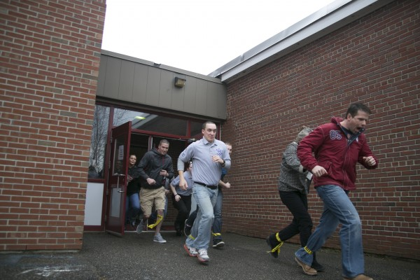 Volunteers run out of Orono High School during a live shooter scenario held by Husson University criminal justice students and Orono fire and police departments  on Saturday.