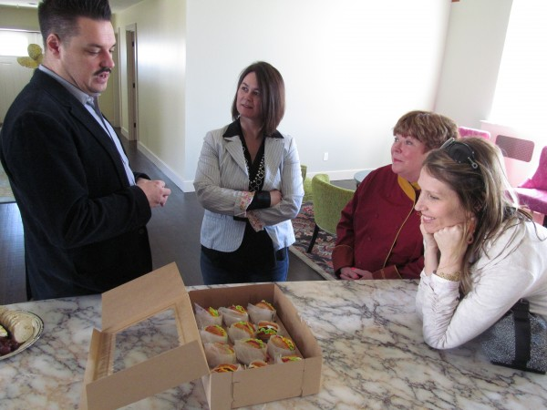 Adam Beckworth of A Little Somethin' Sweet explains his dessert cupcakes, designed to look like cheeseburger sliders, to Marcy Boynton, CVC Catering's Nancy Cerny and Lana Wescott in the Portland kitchen of Tina Richardson. Richardson's firm, Maine Coast Kitchen, designed the space in the center of an old church, which Richardson now lives in