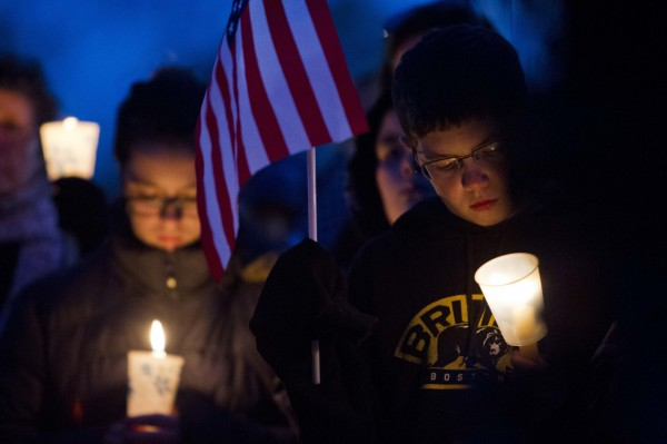 People hold candles during a vigil for slain MIT police officer Sean Collier at the Town Common in Wilmington, Mass., Saturday.