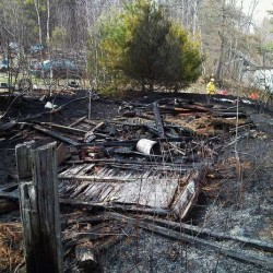 A Strickland Loop Road homeowner who set a test fire on Saturday afternoon called for help when the unpermitted burn became a wildfire and destroyed his shed and about an acre of grass and brush, Jeff Currier, regional forest ranger of the Maine Forest Service, said Saturday in a news report.