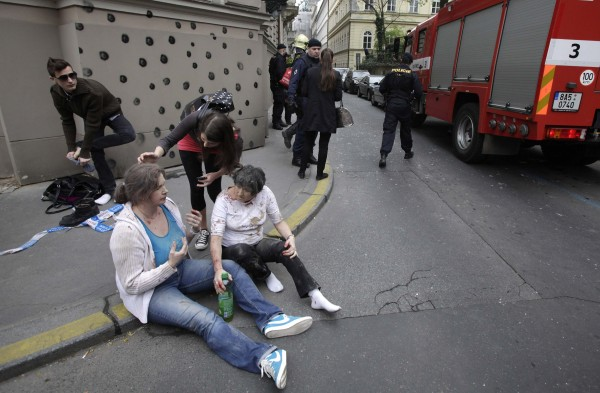 Injured people sit on a sidewalk near the area of a blast after an explosion in Prague on Monday.