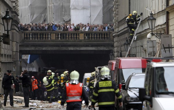 Firefighters search the area after an explosion in Prague on Monday. The explosion in central Prague injured about a dozen people and others were trapped in a building damaged by the blast, emergency services officials said.