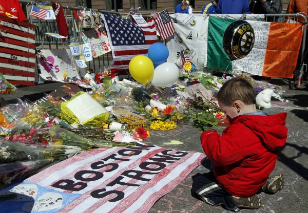 Two-year-old Wesley Brillant of Natick, Massachusetts kneels in front of a memorial to the victims of the Boston Marathon bombings near the scene of the blasts on Boylston Street in Boston, Massachusetts, April 21, 2013.