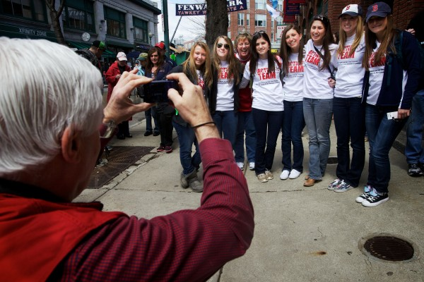 Glenn Michaels, Volunteers of America Northern New England director of marketing and communications, takes a picture of high school student volunteers while on a trip to Fenway Park on Saturday.