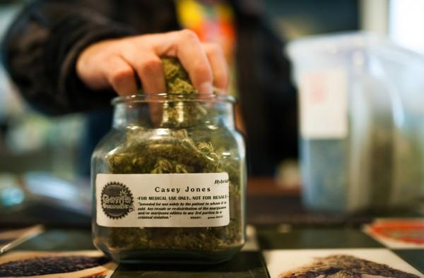 An employee of Ganja Gourmet in Denver, Colo., restocks &quottop shelf&quot medical marijuana on April, 17, 2013.