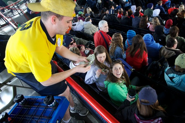 Mark Hooten delivers hot chocolate to York High School students Meaghan Hamel (left) and Adley Palreiro at Fenway Park on Saturday while the students were on a reward trip for working with Volunteers of America Northern New England.