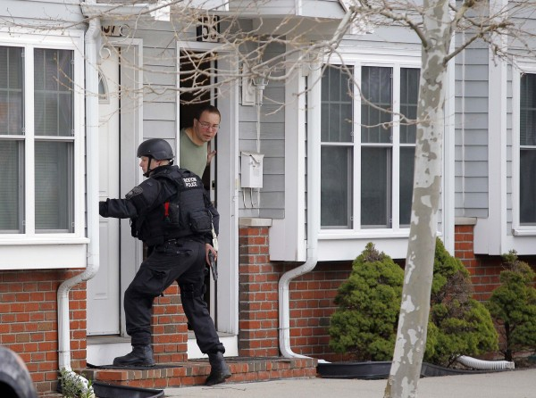 A man looks out of his door as a SWAT team member knocks on his neighbors door as they search for the remaining suspect in the Boston Marathon bombings in Watertown, Mass.