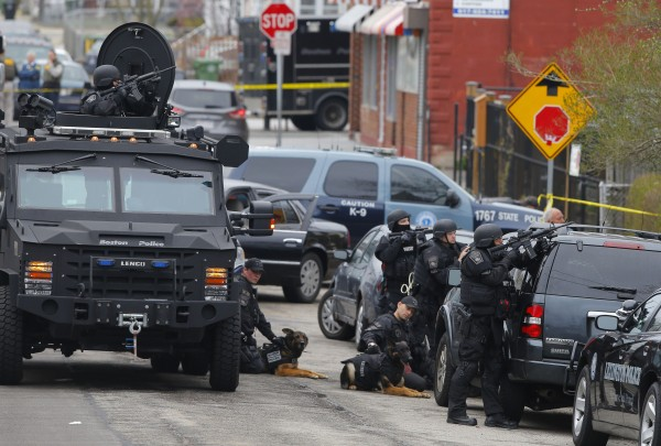 Police officers take position during a search for the Boston Marathon bombing suspects in Watertown, Mass.