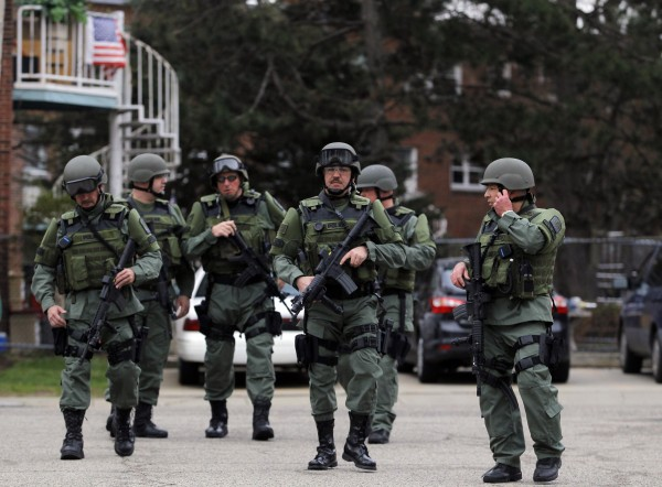 SWAT teams enter a suburban neighborhood to search for the remaining suspect in the Boston Marathon bombings in Watertown, Mass.