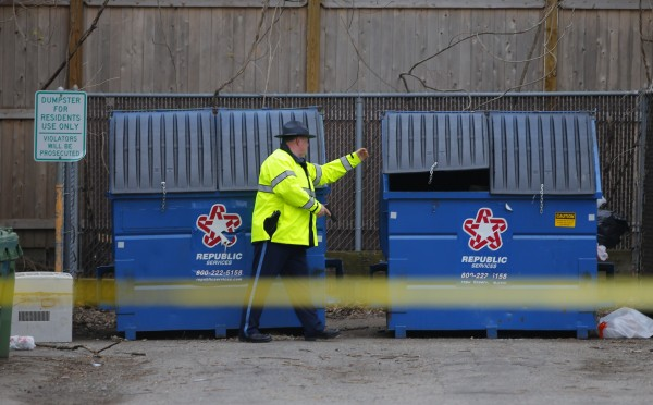 A police officer checks dumpsters during a search for the Boston Marathon bombing suspects in Watertown, Mass.