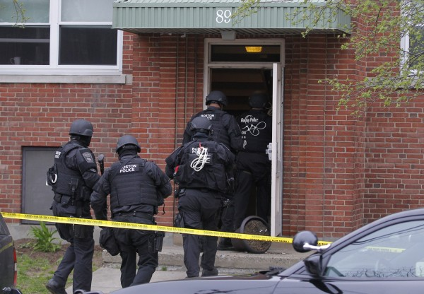 Members of the SWAT enter an apartment as they search for the remaining suspect in the Boston Marathon bombings in Watertown, Mass.