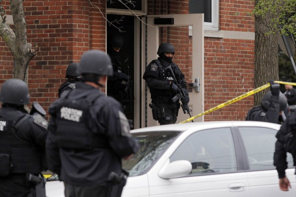 Members of the SWAT team cover an apartment as they search for the remaining suspect in the Boston Marathon bombings in Watertown, Mass.