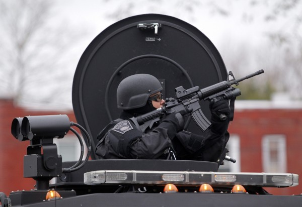 A member of the SWAT team trains a gun on an apartment building during a search for the remaining suspect in the Boston Marathon bombings in Watertown, Mass.