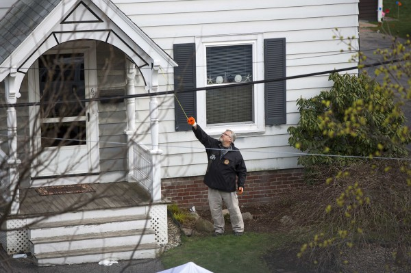 A member of the FBI Evidence Recovery Team works around the home where Boston Marathon bombing suspect Dzhokhar Tsarnaev was hiding at 67 Franklin St. in Watertown, Massachusetts, April 20, 2013.