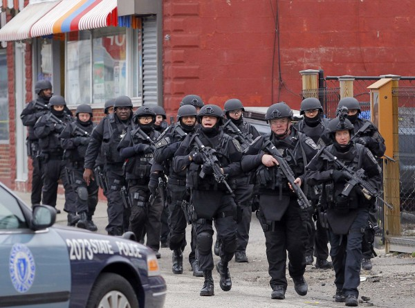 SWAT teams enter a suburban neighborhood to search an apartment for the remaining suspect in the Boston Marathon bombings in Watertown, Mass.