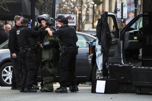Law enforcement bomb technician is helped to put on his protective suit, before he set off controlled detonation during search for suspect in Boston Marathon bombing, in Watertown, Mass.