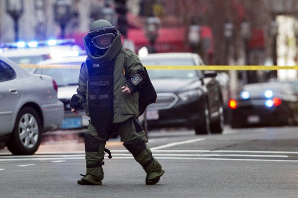 Law enforcement bomb technician walks away after preparing controlled detonation of a suspicious object during a search for a suspect in the Boston Marathon bombing, in Watertown, Mass.
