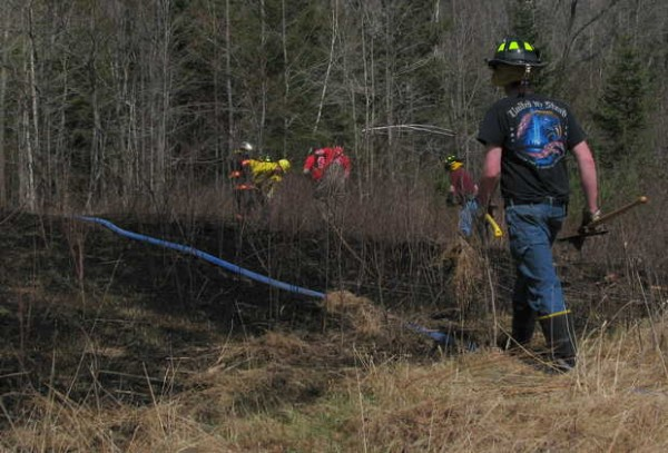 River Valley area firefighters work Friday afternoon to ensure that a woods fire that burned an acre behind a home at 19 Holman Road in Dixfield is completely out.