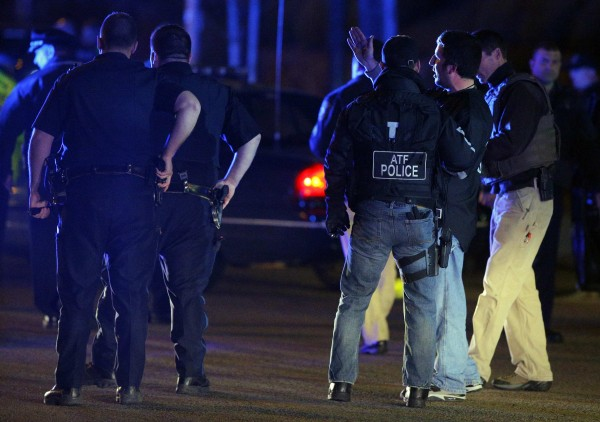 Law enforcement officers talk at the scene of a police manhunt in Watertown, Mass.
