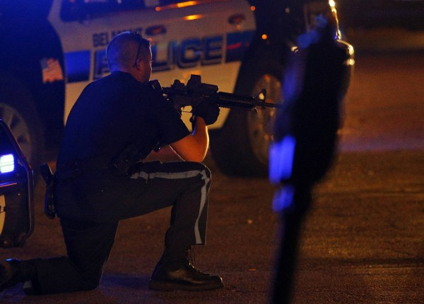 A police officer points his rifle at a man on the ground in Watertown, Mass.