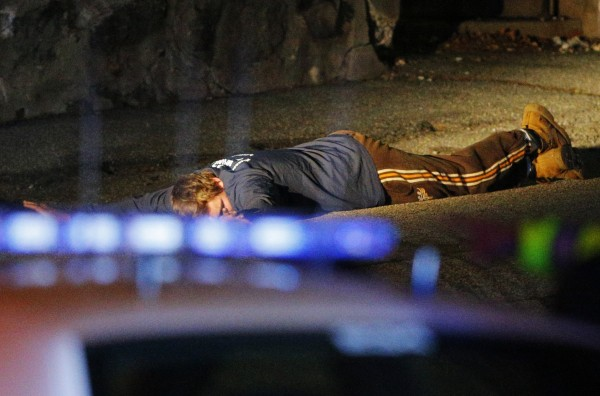 Police officers keep an unidentified man on the ground in Watertown, Mass., April 19, 2013, following the shooting of a police officer at the Massachusetts Institute of Technology.