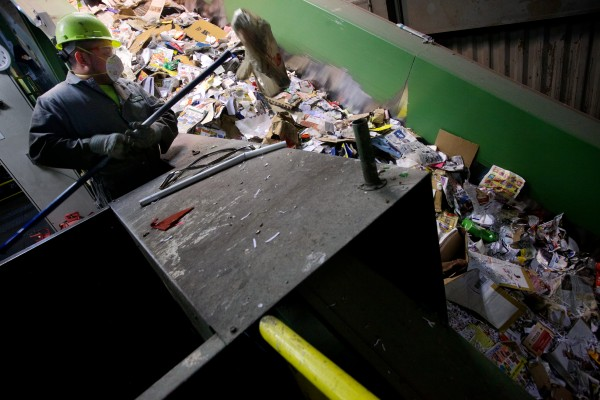 Julio Mejia pulls plastic bags from the recycling steam at ecomaine in Portland. The bags are recyclable but low in value and very hard for the automated machines to sort properly.